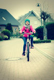 Little girl with bicycle on road.Retro image Stock Photography