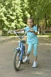 Little girl with bicycle in summer Stock Image