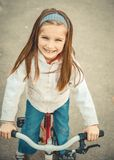 Little girl on a bicycle. In summer park Stock Photos