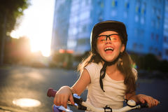 Little girl with bicycle in summer park against sunset Royalty Free Stock Image