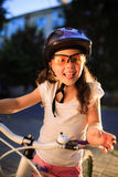 Little girl with bicycle in summer park against sunset Royalty Free Stock Photo
