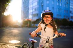 Little girl with bicycle in summer park against sunset Stock Photography