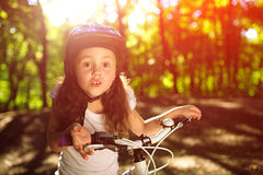 Little girl with bicycle in summer park against sunset. Portrait of a little girl on a bicycle in summer park against sunset Royalty Free Stock Photos