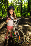 Little girl with bicycle in summer park outdoors. Portrait of a little girl on a bicycle in summer park outdoors Royalty Free Stock Image