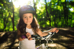 Little girl with bicycle in summer park outdoors Stock Photo