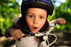 Little girl with bicycle in summer park outdoors Stock Image