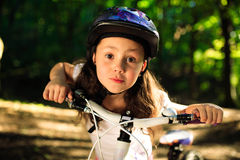 Little girl with bicycle in summer park outdoors Stock Photography