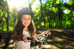 Little girl with bicycle in summer park outdoors Stock Images