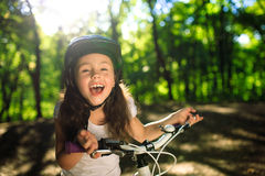 Little girl with bicycle in summer park outdoors Royalty Free Stock Image