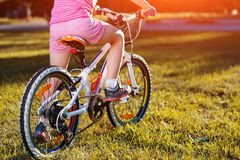 Little girl on a bicycle in summer park Stock Photo