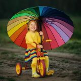 Little girl on the bicycle with umbrella stock image