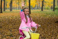 Little girl on a bicycle waving to someone a hand. Little girl in a pink raincoat is riding a bike in the autumn park Royalty Free Stock Photos