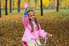 Little girl on a bicycle waving to someone a hand. Little girl in a pink raincoat is riding a bike in the autumn park Stock Image