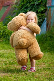 Little girl with big bear Stock Photos