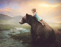 Little girl on a big bear. A little girls climbs on the back of a grizzly bear Stock Images
