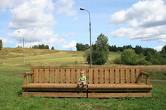 Little girl on a big bench. Day in nature Royalty Free Stock Images