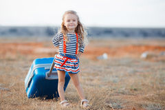 The little girl with a big blue suitcase Royalty Free Stock Photo