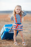 The little girl with a big blue suitcase. A little girl with long blonde curly hair dressed in a striped sailor shirt and knitted skirt with a large blue Stock Photos