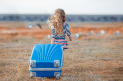 The little girl with a big blue suitcase. A little girl with long blonde curly hair,in a striped shirt and knitted skirt with a large blue suitcase on wheels is Stock Photo