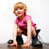 Little girl in big boots. Smiling and standing on a table royalty free stock image