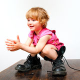 Little girl in big boots. Standing on a table and clapping her hands royalty free stock photos