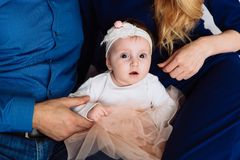 A little girl with big brown eyes sits next to her parents close-up. One year old baby in a beautiful dress and bandage stock photography