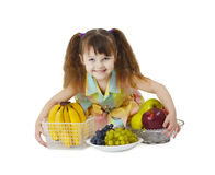 Little girl with big bunch of fruit Stock Image