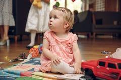 Little girl with a big car sitting on floor stock photos