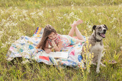 Little girl and big dog. Little girl lies on the rug, reads a book and big friendly dog guards her comfort Royalty Free Stock Images