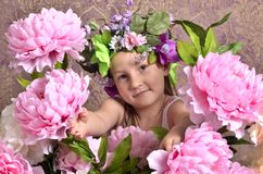 Little girl with big flowers around Stock Photo