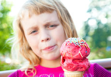 Little girl with big fruit ice-cream in the park Stock Photo