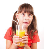 Little girl with a big glass of juice Stock Photography