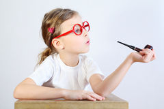Little girl in big glasses sits at table and holds pipeful. Royalty Free Stock Image