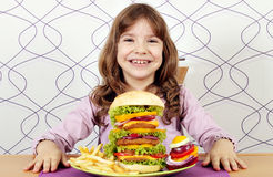 Little girl with big hamburger Royalty Free Stock Photos