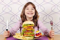 Little girl with big hamburger on table Stock Photos