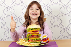 Little girl with big hamburger and thumb up Stock Image
