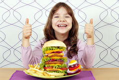 Little girl with big hamburger and thumbs up. Happy little girl with big hamburger and thumbs up royalty free stock images
