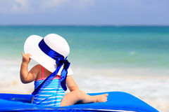 Little girl in big hat on summer beach Stock Photos