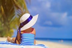 Little girl in big hat on summer beach Stock Photos