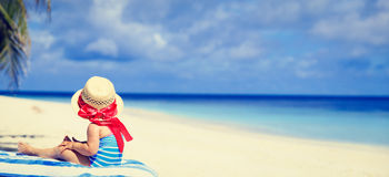 Little girl in big hat on summer beach Stock Photo