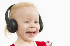 Little girl in big headphones. On white background Royalty Free Stock Images