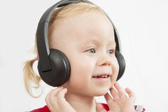 Little girl in big headphones. On white background Royalty Free Stock Photography