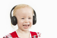 Little girl in big headphones. On white background Stock Images