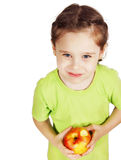 Little girl with a big red apple looks upwards Royalty Free Stock Photography
