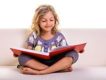 Little girl with big red book Stock Images