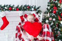 Little girl with big red heart sits in a chair near the Christmas tree Stock Images