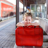 Little girl with big red suitcase on a railway station Stock Photography