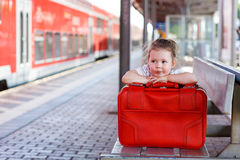 Little girl with big red suitcase on a railway station Royalty Free Stock Photography