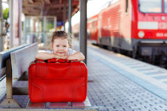 Little girl with big red suitcase on a railway station Royalty Free Stock Photo