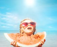 Little girl with big red watermelon segment funny seside portrait stock photo